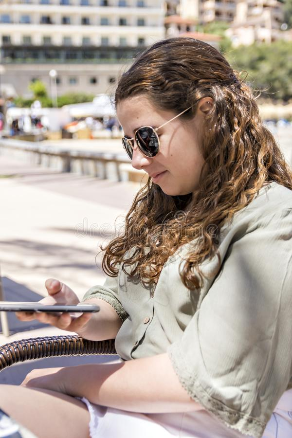 Young girl looking at her cellphone on a spring day stock images