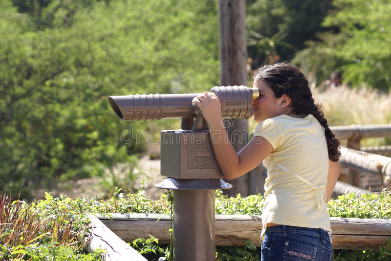 Young girl looking through telescope royalty free stock photography