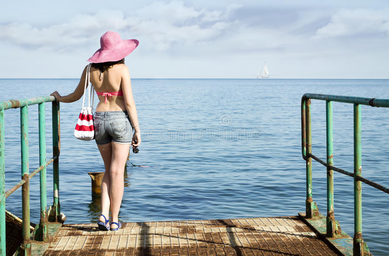 Young girl looking to the sea with a yacht royalty free stock photo