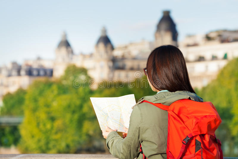 Young girl looking to traveler guide book of Paris stock images
