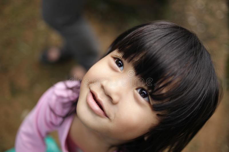 Young Girl Looking Up. Portrait of young Asian girl smiling and looking up, close up image of happy facial expression indonesian malaysian thai little child cute stock photos