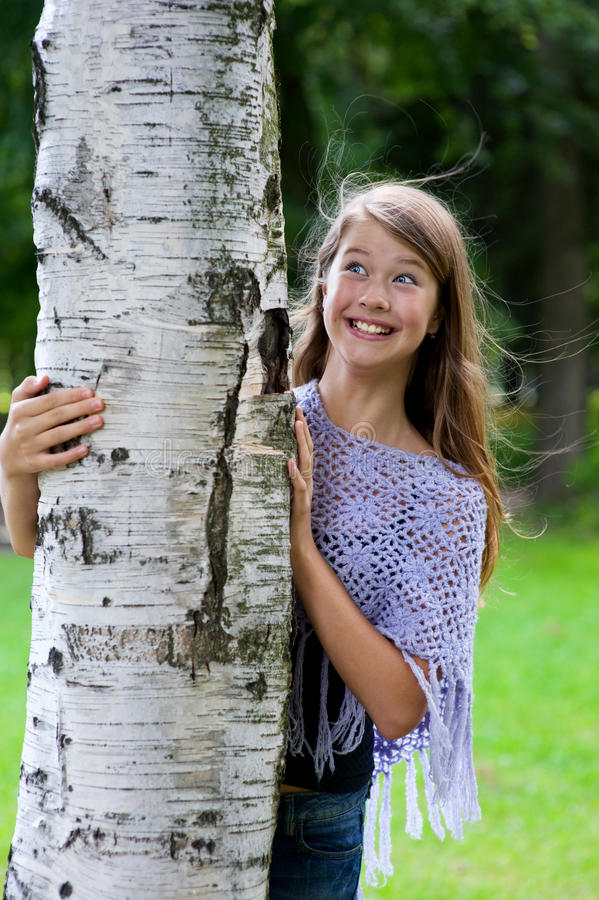 Download Young Girl Looks Out From The Tree Stock Photo - Image of woman, little: 20681172