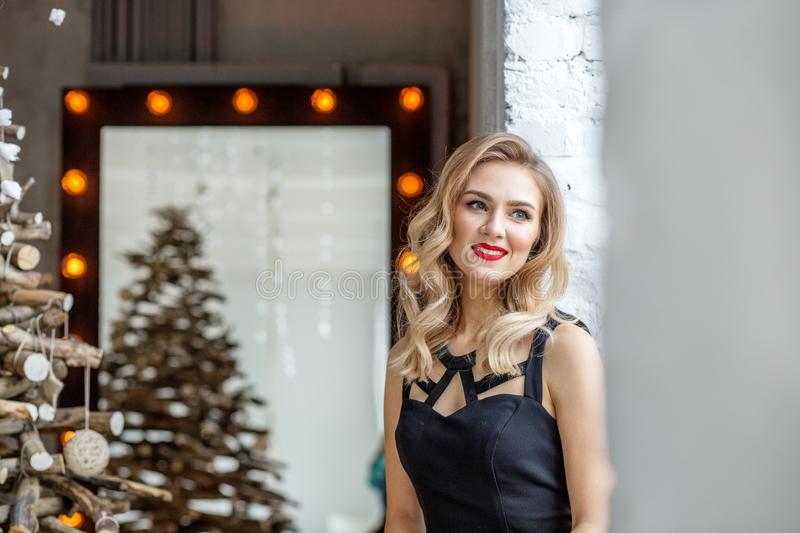 A young girl looks out the window. Red lipstick. Concept of Happy Christmas and New Year, winter, party stock image