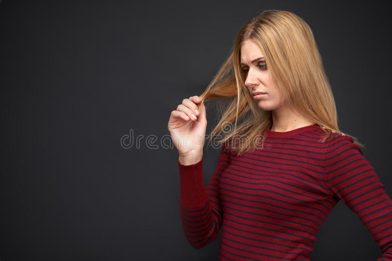 Young girl looks upset at the curls of her hair and thinks about how to give them healthy look and get rid of the split ends royalty free stock photography