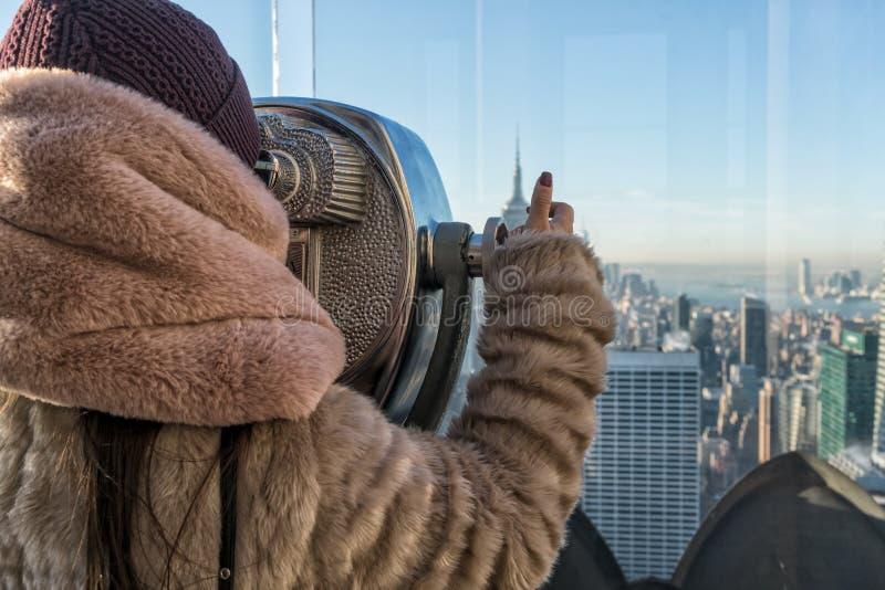 Young Girl Lurking Through Tourist Binoculars Reflecting New York City.Young girl peeking through tourist binoculars with reflecti royalty free stock images