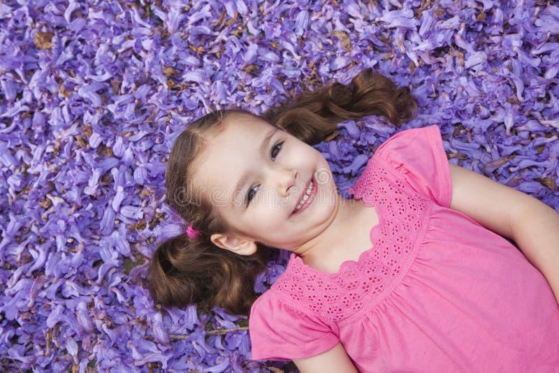 Download Young Girl Lying Among Fallen Purple Flowers Stock Photo - Image of laying, mimosifolia: 11598602