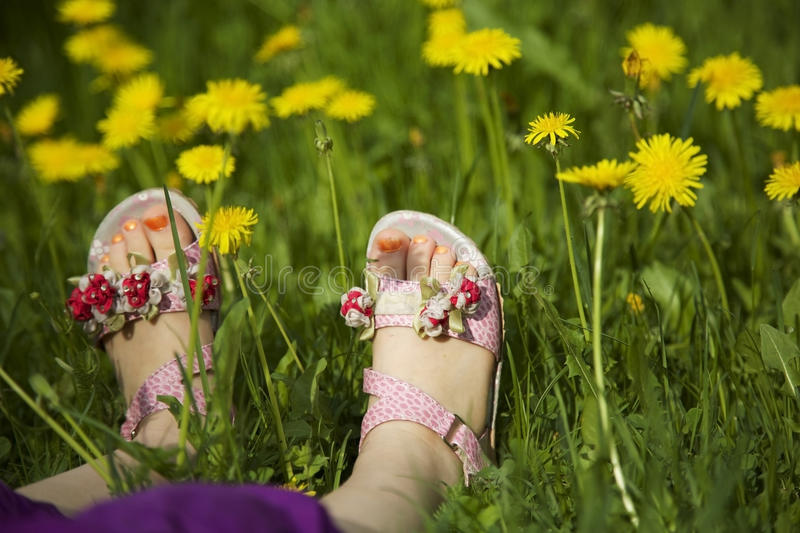 Young girl lying on grass in the middle of dandelions in sunlight with painted toe nails stock photos