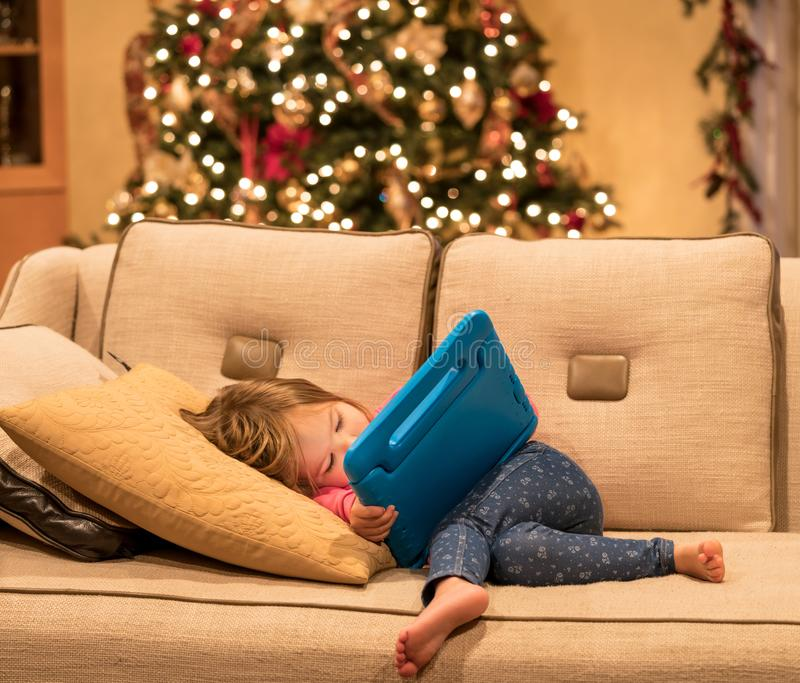 Preschool girl using a tablet computer at home at Christmas. Young girl lying at home on settee and using a child`s tablet touch screen computer at xmas royalty free stock photos