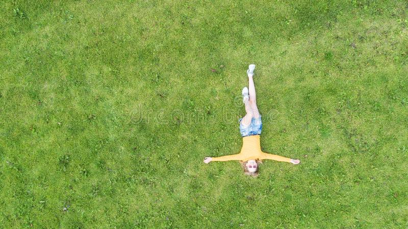 Top view of young girl who relaxing on the grass.  Kid lying in a grass. Copy space stock photo
