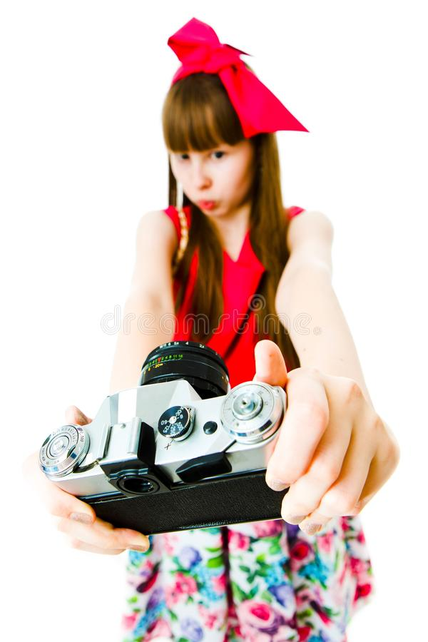 Young girl in magenta dress and ribbon in hairs taking selfie - vintage camera royalty free stock photo