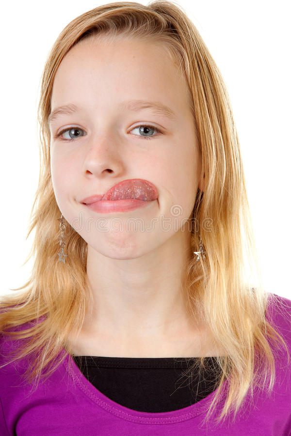 Young girl makes funny face. In closeup over white background royalty free stock image