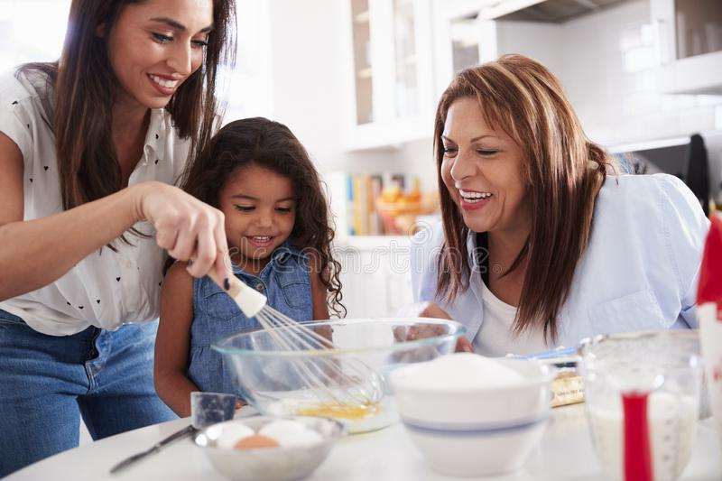 Young girl making a cake in the kitchen with her mum and grandmother, close up stock image