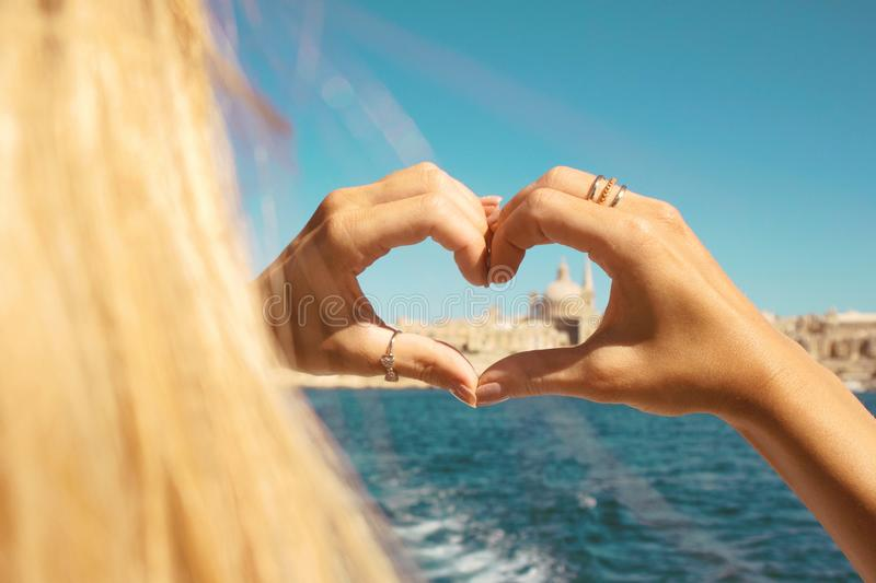 A young girl making heart with hands in rings,symbol of love from the boat at beautiful view on Valletta ,Malta stock photos