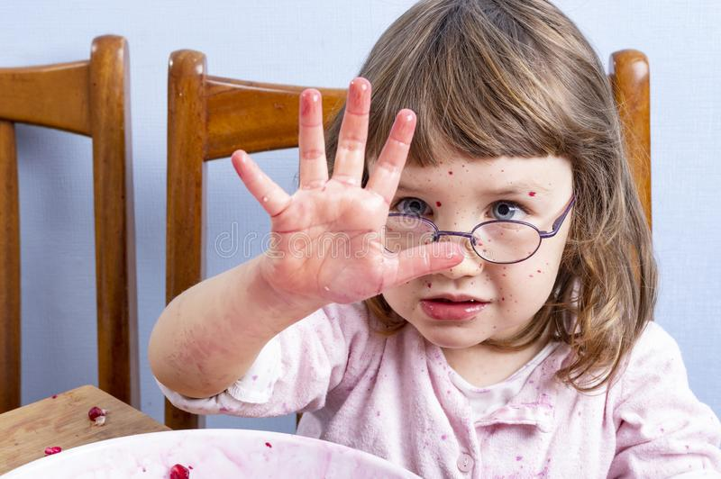 Young girl making a mess. Face and clothes dirty with red spots. Showing a dirty hand on the camera stock image