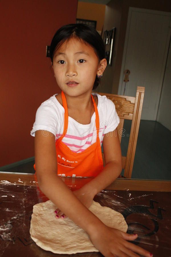 Young girl making pizza stock photo