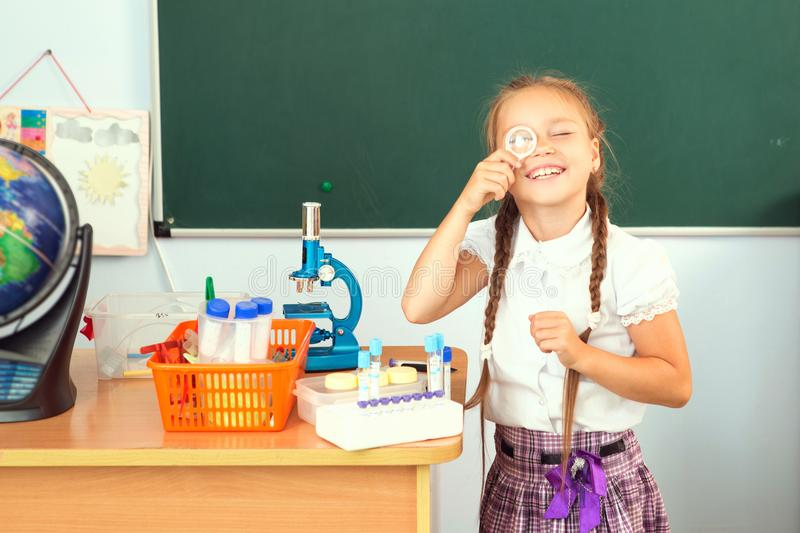 Young girl making science chemistry experiments in school laboratory. Education concept.  stock photography