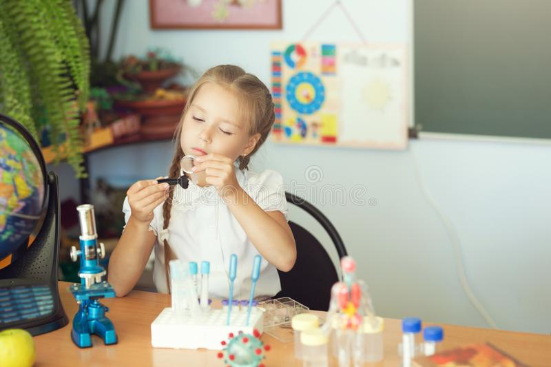 Young girl making science chemistry experiments in school laboratory. Education concept.  royalty free stock photos