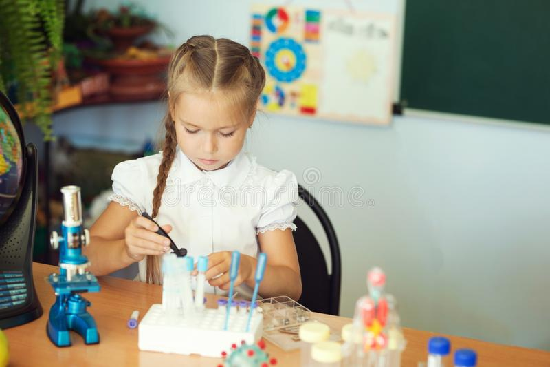 Young girl making science chemistry experiments in school laboratory. Education concept.  stock image
