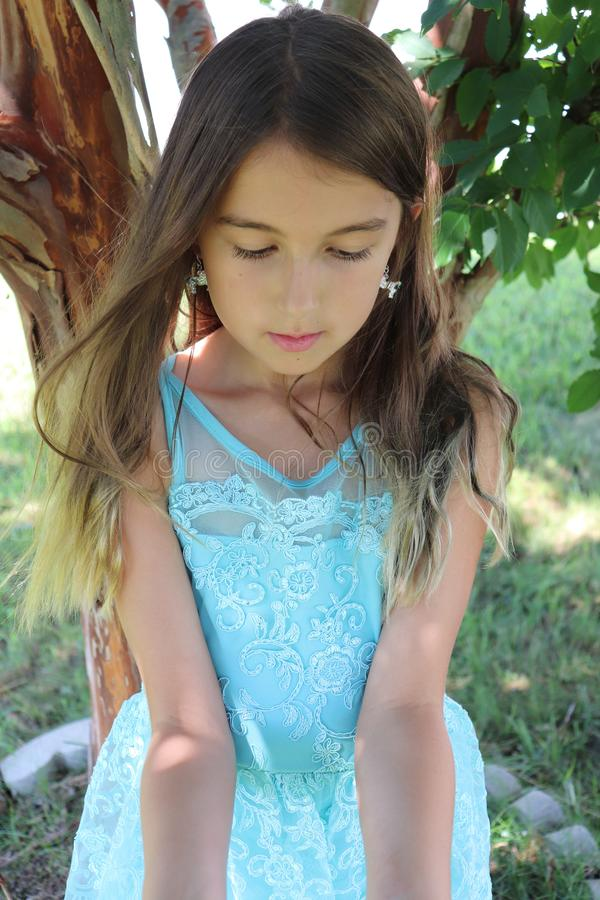 Young Girl Manifests a Magical Life. A young girl in a blue lace and gauze dress opens her arms manifest or summon magical things to come into her life on a stock photos