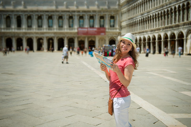 Young girl with map at San Marco square in Venice. Happy young girl with map at San Marco square in Venice royalty free stock image