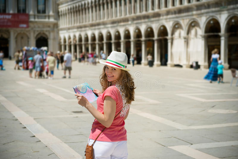 Young girl with map at San Marco square in Venice. Happy young girl with map at San Marco square in Venice royalty free stock images