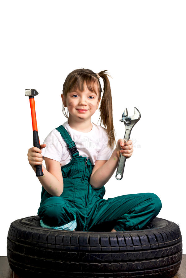 Young girl mechanic. In green clothes with a wheel and hammer royalty free stock photo