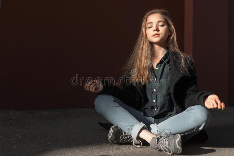 A young girl meditating and breathing in pose of lotus in sunny weather. Concept of getting inner harmony and health stock photos