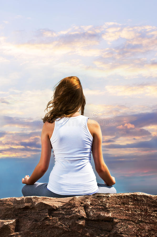 Young girl meditating at sunset stock images