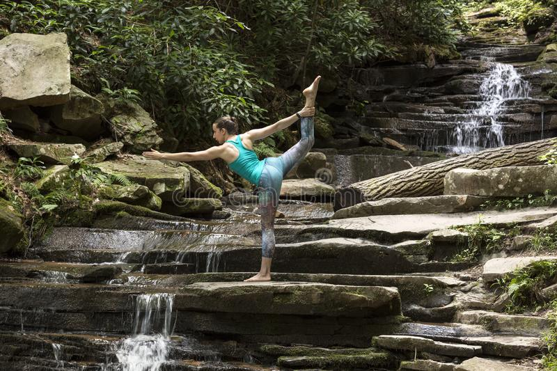 Young girl meditating with yoga in front of waterfall stock photo