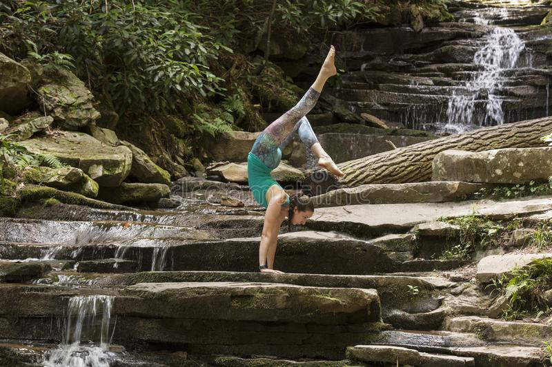 Young girl meditating with yoga in front of waterfall. Young girl performing yoga in nature and in front of a beautiful waterfall in nature while meditating stock photos