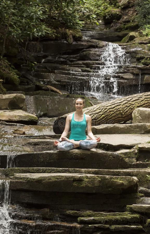 Young girl meditating with yoga in front of waterfall royalty free stock photography