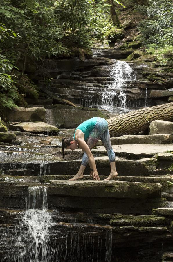 Young girl meditating with yoga in front of waterfall royalty free stock photo
