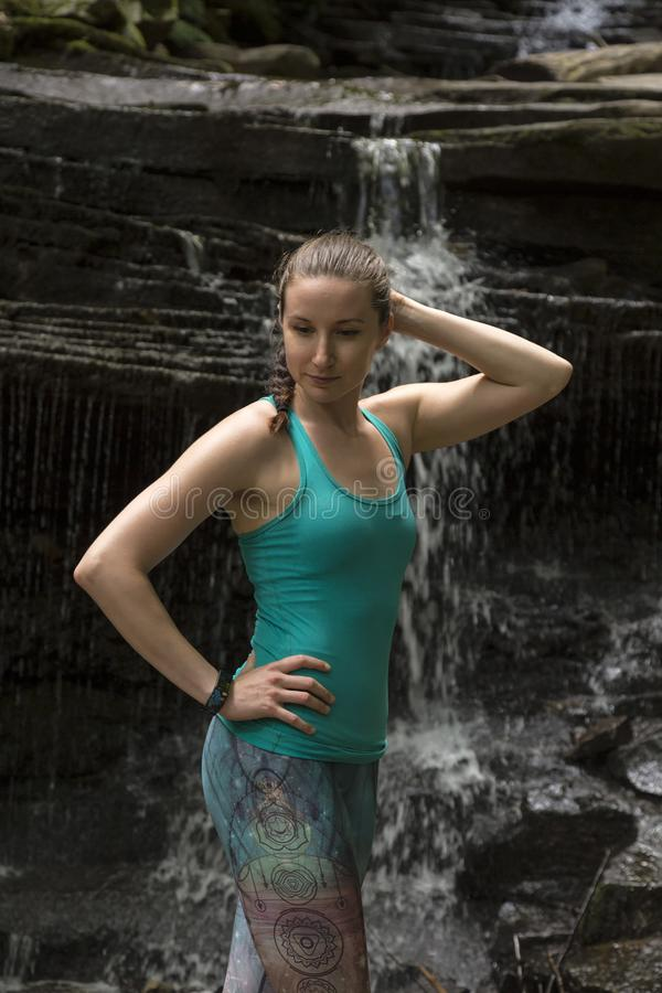 Young girl meditating with yoga in front of waterfall stock photos