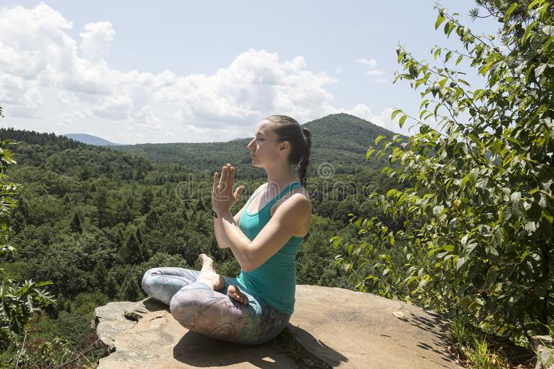 Young girl meditating with yoga on a mountain cliff royalty free stock photos
