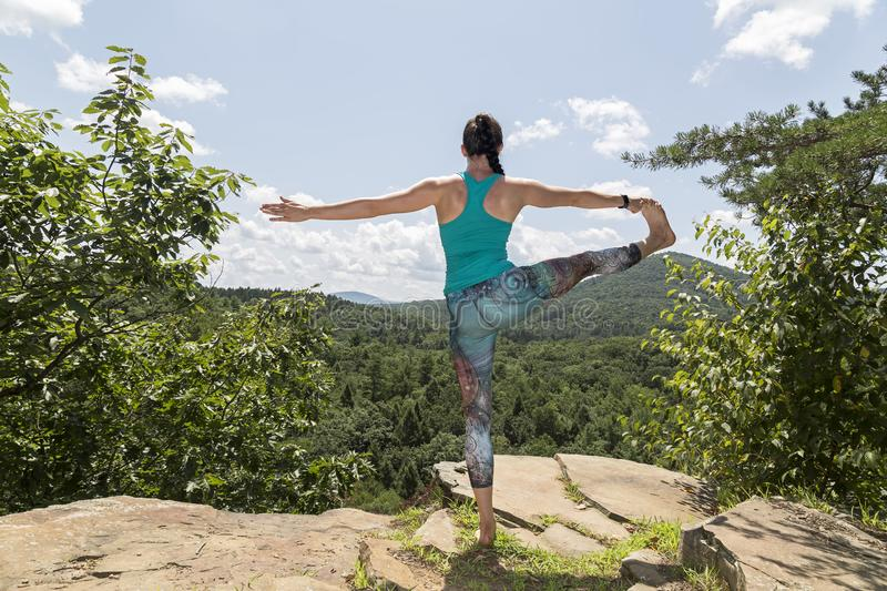 Young girl meditating with yoga on a mountain cliff stock photography