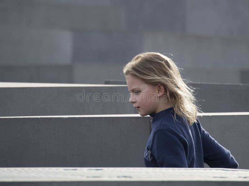 Young girl at the Memorial to the Murdered Jews of Europe, Berlin. The Memorial to the Murdered Jews of Europe, also known as the Holocaust Memorial, is a royalty free stock photography