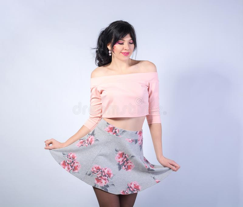 Young girl in a mini skirt smiles on a white background. Young woman with a heart on her cheek in a mini skirt smiles on a white background stock image