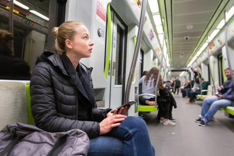 Young girl with mobile phone traveling on metro. stock images