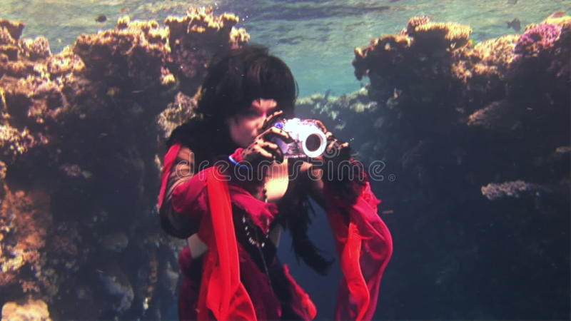Young girl model free diver underwater in red costume of pirate in
