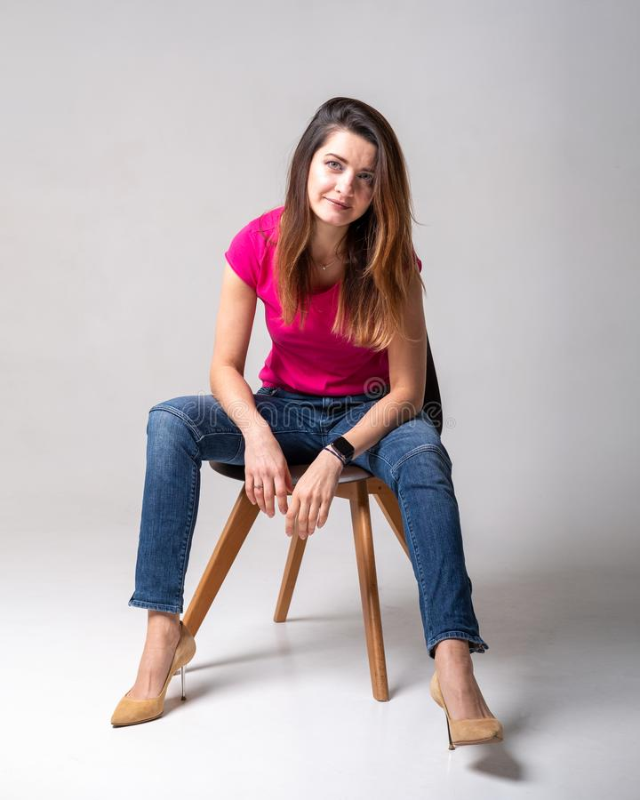Young girl model in pink tank top and blue jeans stock image