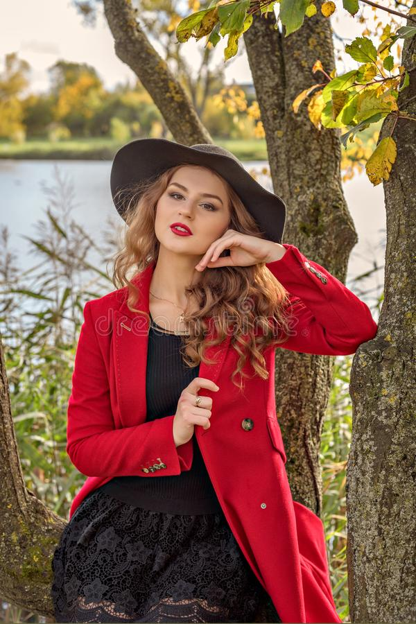 Girl model posing in a red coat and black hat on the branches of a tree on the river bank royalty free stock images