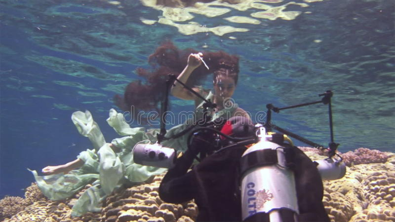 Young girl model underwater poses for camera on background of corals