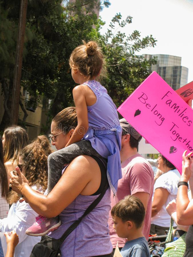 Young girl on mother`s shoulders at U.S. political march stock image