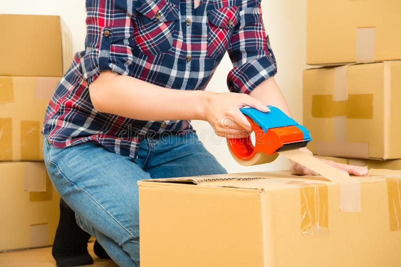 Young girl moving taping boxes stock photography