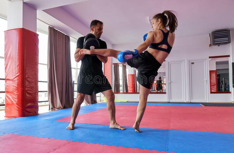 FIghter girl and coach. Young girl muay thai fighter and her coach hitting mitts in the ring stock photo