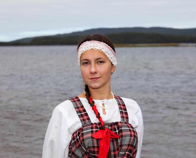 Young girl in national dress at the river shore stock photography