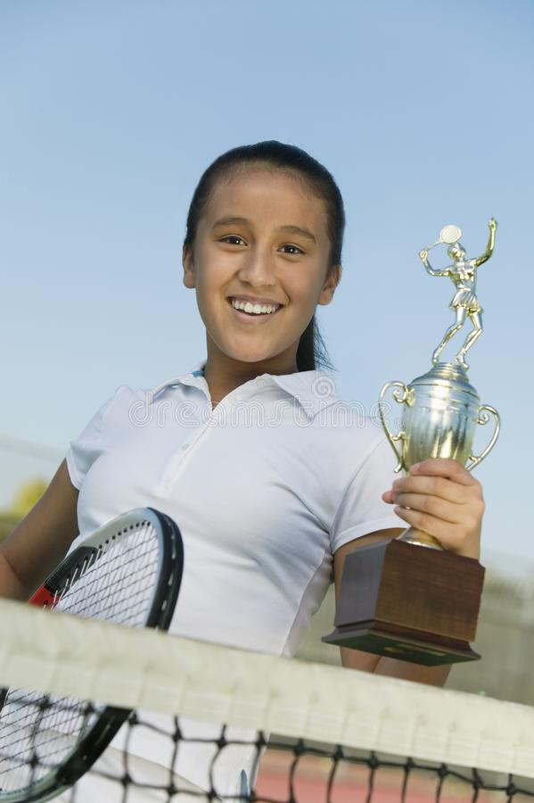Young girl at net on tennis court holding trophy