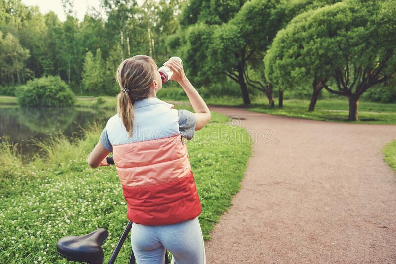 Young girl next to her bike drinking water with a bottle in a park. While having a break stock photo