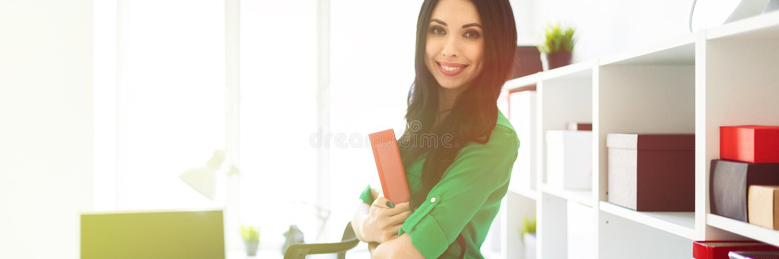A young girl in the office is holding a folder with documents. stock photos