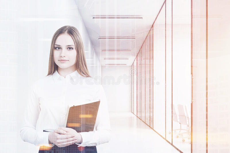 Young girl in an office suit is holding a black folder and standing in a white office corridor with conference rooms. 3d rendering. Mock up. Toned image royalty free illustration